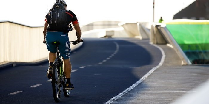 Man bicycling over a bridge