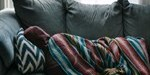 Depression, person sleeping in sofa with a hoodie and blanket